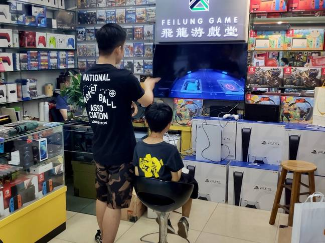 Customers in a store in the electronics shopping area of Huanqiangbei in Shenzhen, with a stack of PS5s clearly visible / Credit: Daniel Camilo
